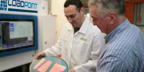 Lab technician showing customer precision cut optical material